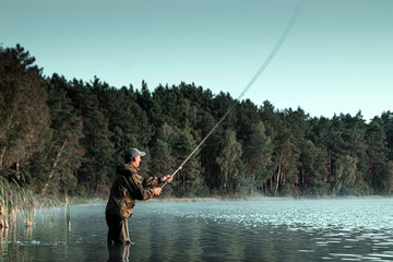Poster Peche A male fisherman on the lake is standing in the water and fishing for a fishing rod. Fishing hobby vacation concept. Copy space.