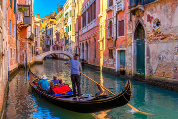 Narrow canal with gondola and bridge in Venice, Italy. Architecture and landmark of Venice. Cozy cityscape of Venice. Fotomurales