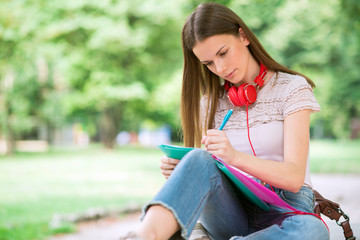 Portrait of a female student studying in a park in front of the school