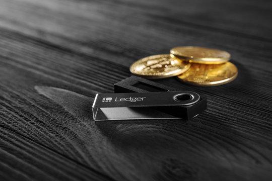 UKRAINE, ROVNO - On 23 September: Ledger hardware wallet for cryptocurrency on a wood background