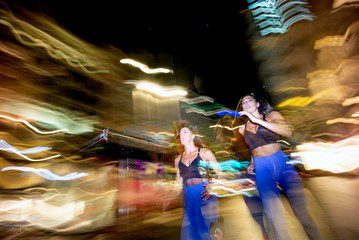 Long exposure photo of two women running in the city at night