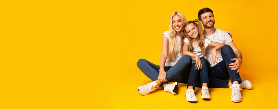 Family Embracing Sitting On Floor Over Yellow Background, Panorama