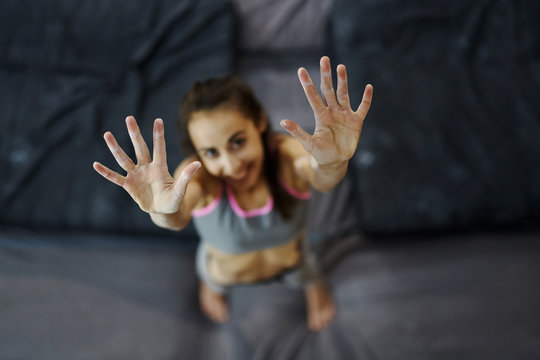 portrait of smiling young woman with muscular naked torso climber at inside climbing gym. Hands with white chalk powder. Top view of hands.
