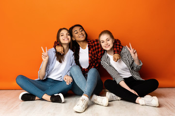Excited teen girls showing peace gestures and smiling