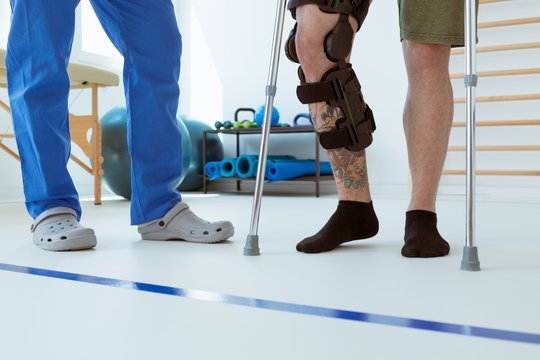 Man after car accident in an orthosis and on crutches learning to walk in the clinic, helpful therapist near him