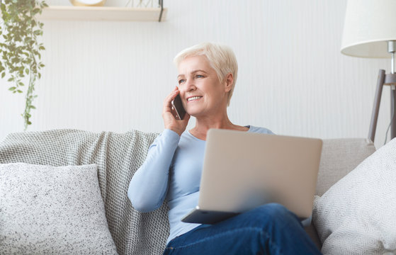 Modern senior woman holding laptop and talking by phone