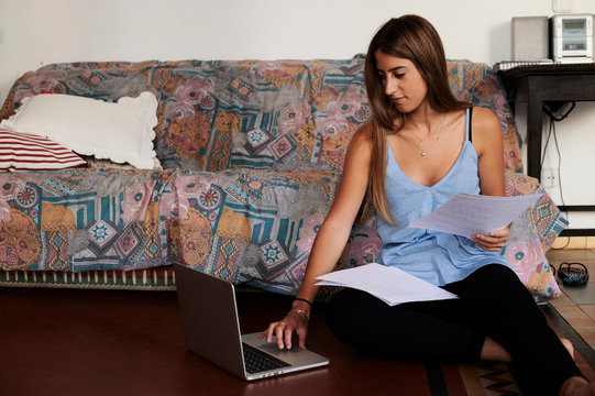 Female student studying at home, using laptop