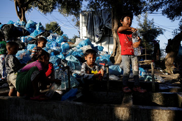 Children fill bottles with water next to a pile of garbage at a makeshift camp for refugees and migrants next to the Moria camp on the island of Lesbos