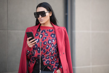 Business stylish woman in red clothes. Smartphone in her hands. City Style