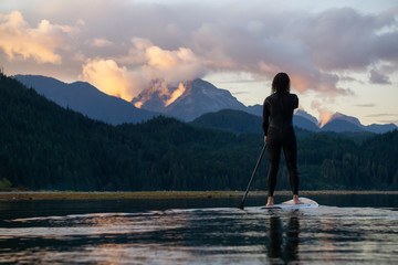 Wall Mural - Adventurous Girl on a Paddle Board is paddling in a calm lake with mountains in the background during a colorful summer sunset. Taken in Stave Lake near Vancouver, BC, Canada.