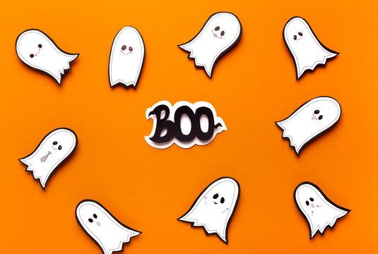 Spooktacular Halloween ghosts flying on orange background