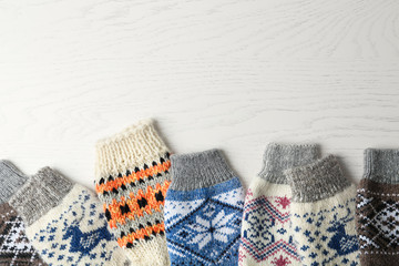 Fototapete - Soft knitted socks on white wooden background, flat lay with space for text. Winter clothes
