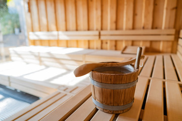 indoor of a Finnish sauna, with a water bucket and sunlight shining through a big window, Spa and Wellness concept in a hotel