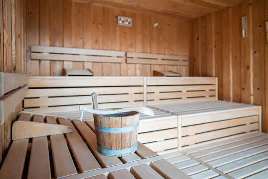 interior of a Finnish sauna, with a wooden water bucket, Spa and Wellness concept in a hotel