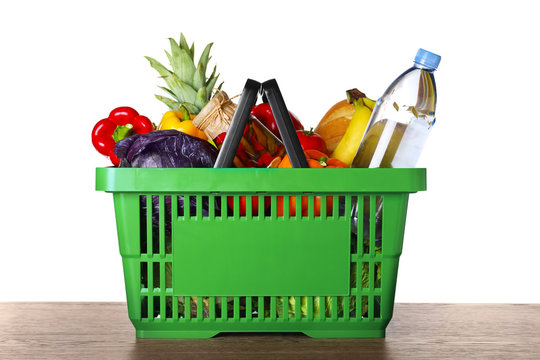 Shopping basket with grocery products on wooden table against white background