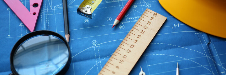 Engineering blueprint design for buildings of blue architecture tools ruler magnifying glass to achieve a human activity hard hat concept