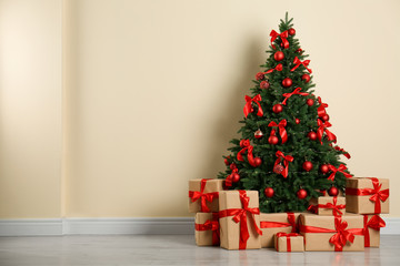 Fotobehang - Decorated Christmas tree and gift boxes near beige wall. Space for text