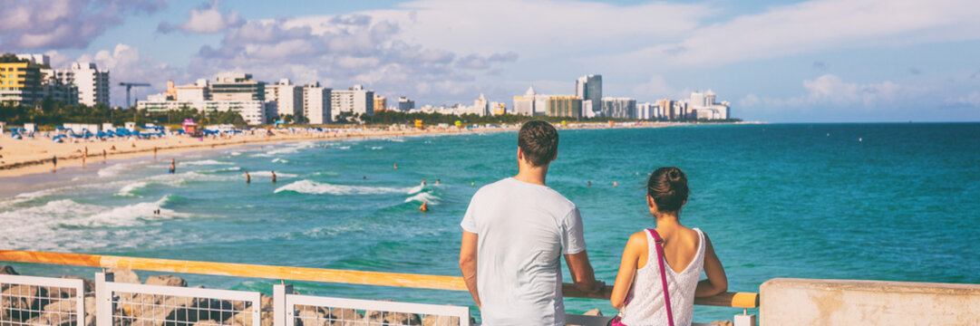 Miami beach people lifestyle young tourists couple walking in South Beach, Miami, Florida. USA travel. Panoramic banner background.