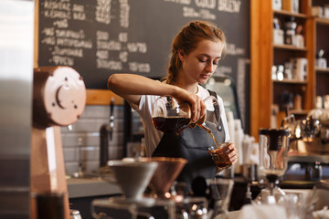 Fototapeta Professional barista preparing coffee using chemex pour over coffee maker and drip kettle. Young woman making coffee. Alternative ways of brewing coffee. Coffee shop concept. obraz