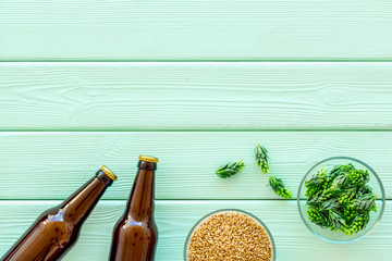 Barley and hop for making beer on green wooden background top view copy space