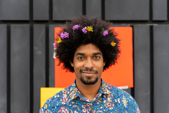 Portrait of man with blossoms in his hair wearing colorful shirt