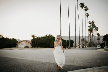 Rear view of bride on a road with palm trees