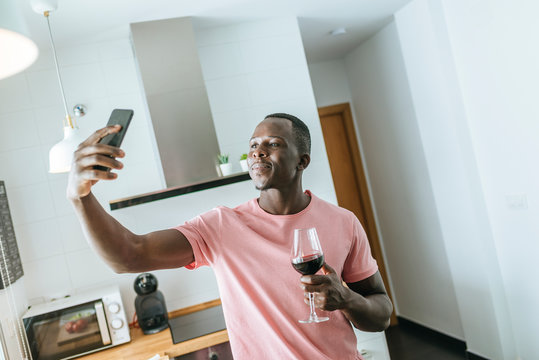 Young man with wine glass taking a selfie in kitchen
