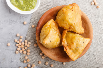 traditional indian food samosa in wooden  plate with mint chutney on a gray concrete background. top view.