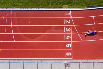 Aerial view of a young female, athlete lying on a tartan track after crossing the finishing line