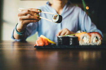 Close-up of a woman eating sushi in a restaurant