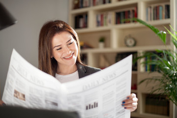 young woman reading a newspaper at office