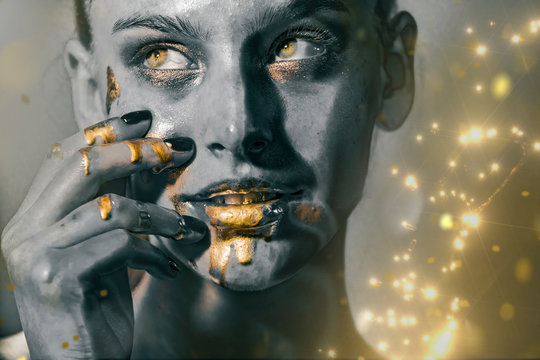 Gold Paint smudges drips from woman face, lips and hand, lipgloss   dripping from sexy lips, golden liquid drops on beautiful model girl's   mouth, gold metallic skin make-up