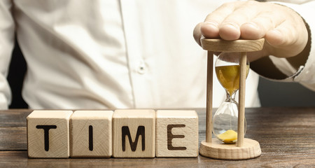 A man puts hourglass near wooden blocks with the word Time. Concept of time management and proper...