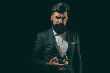 Bearded handsome man holding glass of cognac. Alcohol concept. Alcohol Drink. Retro vintage man with cognac or scotch.