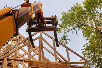 A wooden roof truss being lifted by a boom truck forklift in the roof a new home