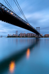 View on Brooklyn Bridge and Downtown Manhattan on a cloudy morning with long exposure