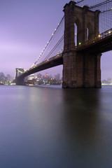 View on Brooklyn bridge and Dumbo neighborhood on a foggy sunset with long exposure