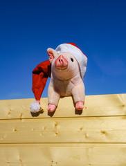 Ferkelstofftier mit Nikolausmütze hängt an einer Bretterwand
