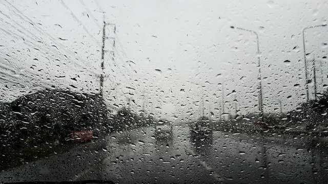 drops of rain drizzle on the glass windshield in the morning