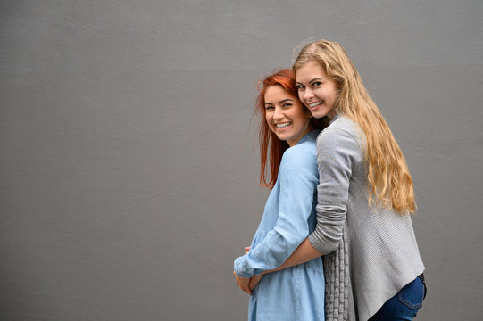 Same-sex relationships. A red-haired pregnant woman in a denim dress is standing against a gray wall, her hand is resting under her tummy. Her wife gently hugged the expectant mother from behind.