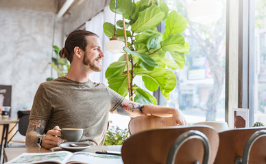 Portrait of handsome bearded caucasian man with tattoo at modern coffee shop.Guy sitting in vintage cafe relaxing. Freelance people lifestyle with copy space concept.