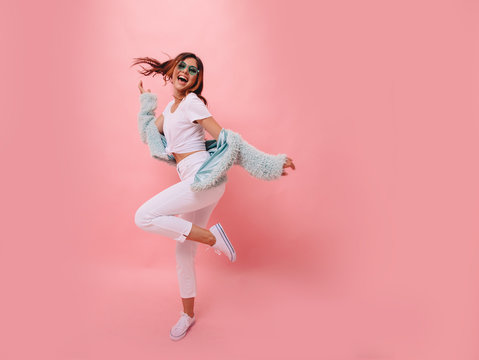 Inspired positive girl in white sneakers dancing on pink background. Gorgeous young female model with dark wavy hair jumping in studio. Not isolated. Copy space.