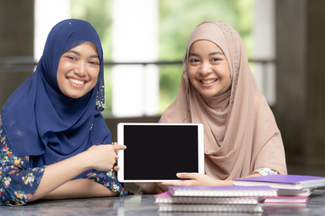 Teenager muslim students with tablet