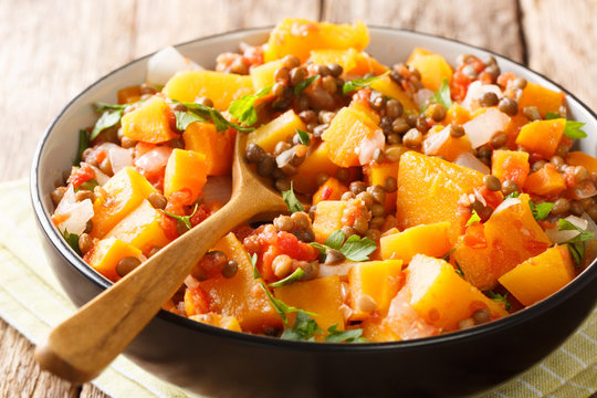 Spicy vegetable stew of pumpkins, tomatoes, lentils, onions and carrots close-up in a bowl. horizontal