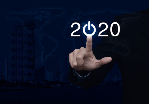 Businessman pressing 2020 start up business flat icon over world map, modern city tower and skyscraper, Business happy new year cover, Elements of this image furnished by NASA