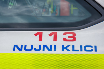 Police sign with emergency dial number on the side of patrol car