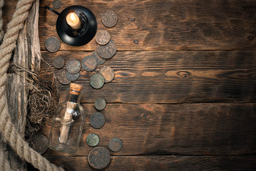 Pirate letter parchment in a glass bottle on brown wooden table background.
