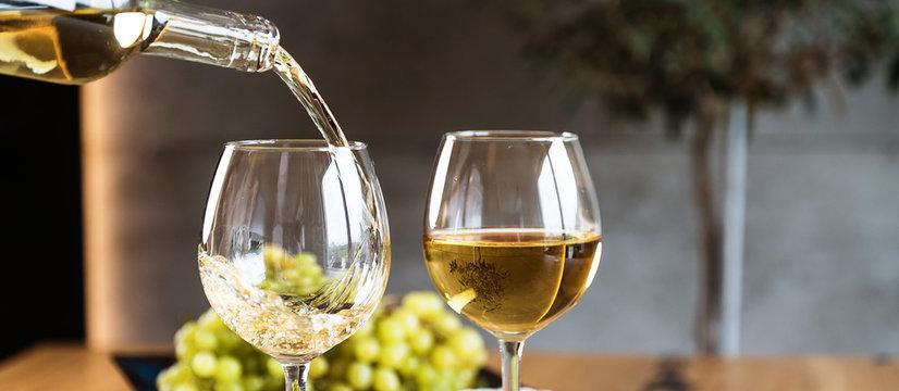 Waiter pouring white wine into wineglass.