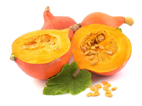 Fresh pumpkin vegetable with green leaves and seeds isolated on white background. Hokaido squash.