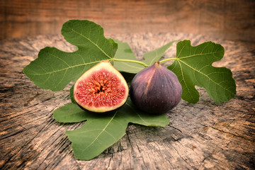 Fresh figs on old wooden background. Fruit - fig with leaves.